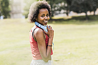 Portrait of smiling sporty young woman in park - UUF11587
