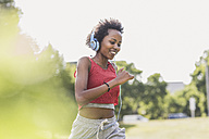 Young woman with headphones running in park - UUF11590