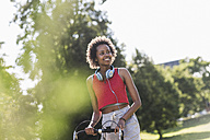 Smiling sporty young woman with bicycle in park - UUF11593