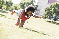 Young woman exercising on meadow in park - UUF11596