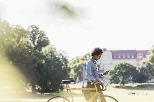 Young woman with cell phone pushing bicycle in park - UUF11605