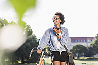 Smiling young woman with cell phone and bicycle in park - UUF11608