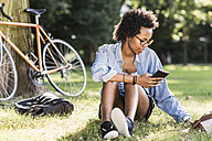 Young woman resting in park with cell phone and tablet - UUF11614