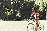 Smiling young woman riding bicycle in park - UUF11617