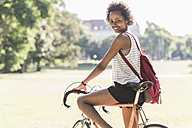 Portrait of smiling young woman on bicycle in park - UUF11620