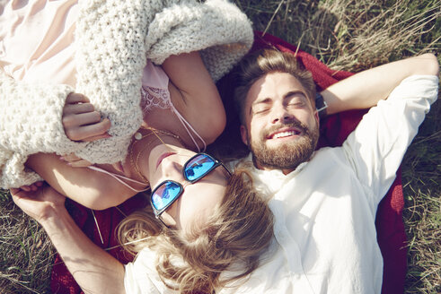 Happy young couple lying in grass - ABIF00019