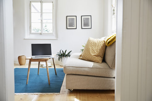 Laptop on coffee table in a bright modern living room in an old country house - PDF01273