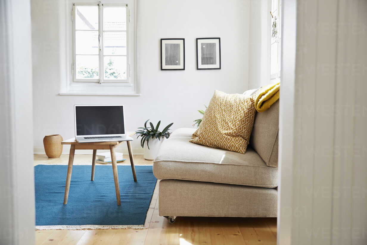 Laptop on coffee table in a bright modern living room in an old country house - PDF01273 - Philipp Dimitri/Westend61