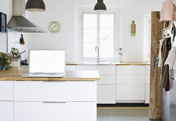 Laptop standing on worktop in a modern kitchen - PDF01276