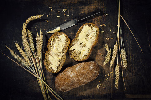 Buttered bread and ear of wheat on dark wood - MAEF12403