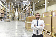 Portrait of confident businessman standing in warehouse - LYF00759
