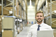 Portrait of confident businessman with laptop in warehouse - LYF00762