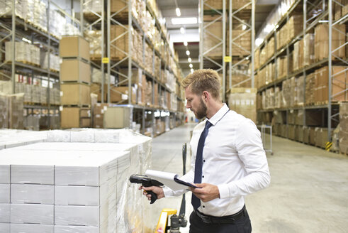 Businessman with clipboard in warehouse scanning goods - LYF00765
