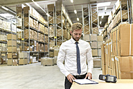 Businessman with clipboard and barcode scanner in warehouse - LYF00768