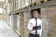 Businessman looking at clipboard in warehouse - LYF00771