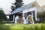 Happy mature couple lying on meadow in front of their house - RIBF00670