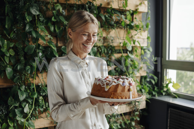 Smiling businesswoman holding birthday cake in green office - JOSF01367