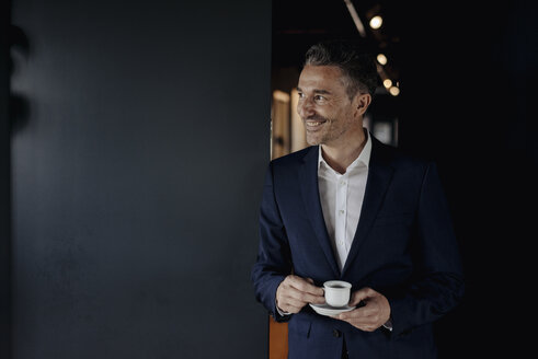 Smiling businessman with espresso cup looking sideways - JOSF01385