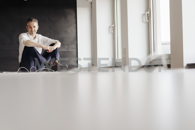 Businessman in office sitting on the floor - JOSF01397