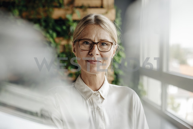 Portrait of businesswoman in green office at the window - JOSF01409