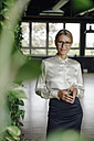 Portrait of confident businesswoman in green office - JOSF01418