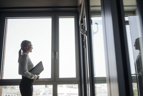Businesswoman in office looking out of window - JOSF01430