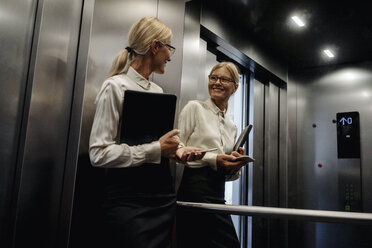 Smiling businesswoman looking in mirror in elevator - JOSF01433