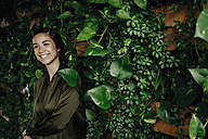 Happy young woman at wall with climbing plants - JOSF01448