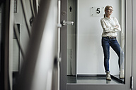 Businesswoman standing on the corridor looking out of window - JOSF01487