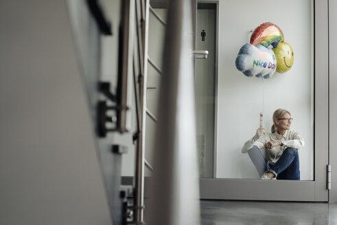 Businesswoman sitting on corridor holding balloon - JOSF01490