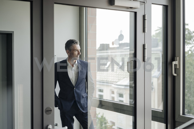Businessman in office looking out of window - JOSF01493