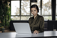 Young woman using laptop in office - JOSF01508