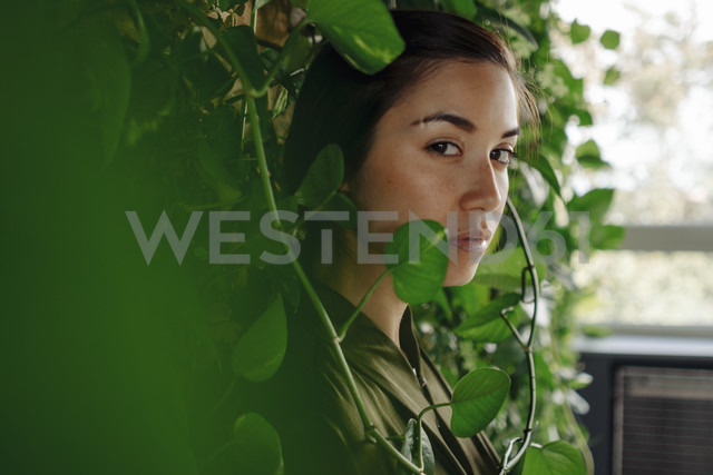 Portait of young woman at wall with climbing plants - JOSF01511
