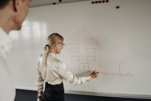 Businesswoman drawing house on whiteboard - JOSF01514