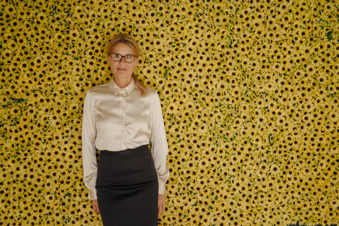 Portrait of businesswoman standing at wall with sunflowers - JOSF01520