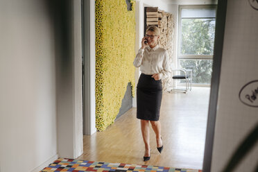Smiling businesswoman on cell phone on office floor - JOSF01523
