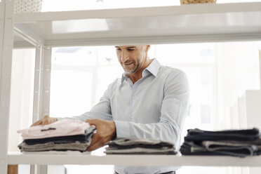 Businessman sorting clothes on shelf - KNSF02421