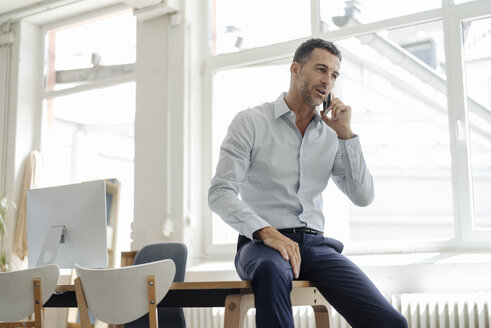 Businessman in office talking on cell phone - KNSF02427