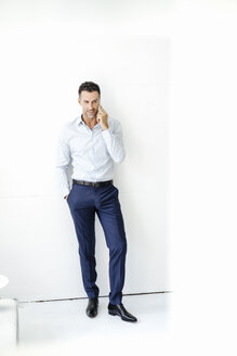 Businessman standing at a wall talking on cell phone - KNSF02436