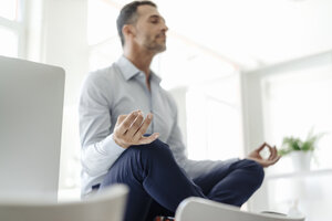Businessman sitting on table in office practising yoga - KNSF02439