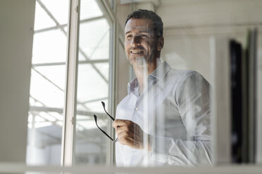 Smiling businessman holding glasses standing at the window - KNSF02457