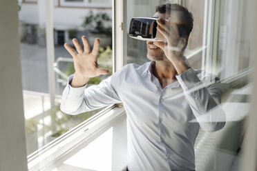 Businessman at the window wearing VR glasses - KNSF02463