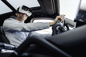 Businessman wearing VR glasses driving a car - KNSF02472