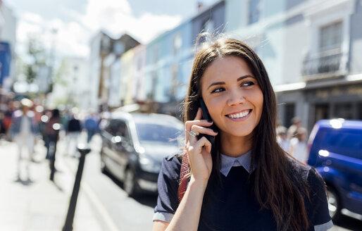UK, London, Portobello Road, portrait of smiling woman on the phone - MGOF03575
