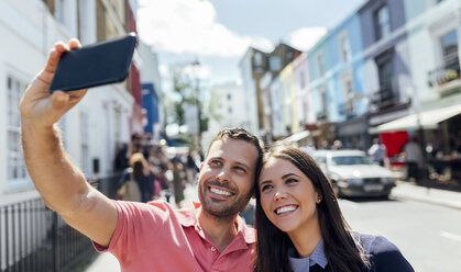 UK, London, Portobello Road, happy couple taking selfie with cell phone - MGOF03578