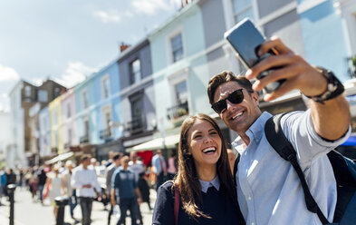 UK, London, Portobello Road, portrait of laughing couple taking selfie with smartphone - MGOF03581