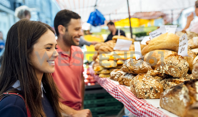 UK, London, Portobello Road, smiling young woman at bread stand - MGOF03590