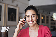 Mature woman sitting in cafe, talking on the phone - WESTF23546