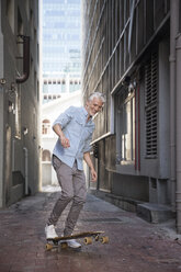 Mature man with longboard in an alley - WESTF23555