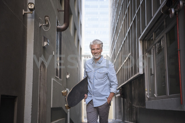 Mature man with longboard in an alley - WESTF23558